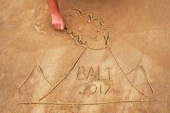 Abbildung auf Sand Gezogener Vulkan mit Text Bali nach innen Stockbild