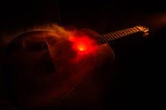 Abbildung der elektrischen Gitarre Akustikgitarre auf einem dunklen Hintergrund unter Lichtstrahl mit Rauche mit Kopienraum Gitar Lizenzfreies Stockfoto