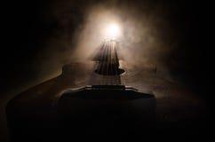 Abbildung der elektrischen Gitarre Akustikgitarre auf einem dunklen Hintergrund unter Lichtstrahl mit Rauche mit Kopienraum Gitar Stockbild