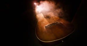 Abbildung der elektrischen Gitarre Akustikgitarre auf einem dunklen Hintergrund unter Lichtstrahl mit Rauche mit Kopienraum Gitar Lizenzfreies Stockbild