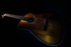 Abbildung der elektrischen Gitarre Akustikgitarre auf einem dunklen Hintergrund unter Lichtstrahl mit Rauche mit Kopienraum Gitar Lizenzfreie Stockfotografie