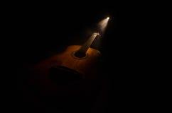 Abbildung der elektrischen Gitarre Akustikgitarre auf einem dunklen Hintergrund unter Lichtstrahl mit Rauche mit Kopienraum Gitar Stockfoto