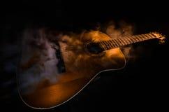 Abbildung der elektrischen Gitarre Akustikgitarre auf einem dunklen Hintergrund unter Lichtstrahl mit Rauche mit Kopienraum Gitar Lizenzfreie Stockfotos