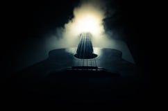 Abbildung der elektrischen Gitarre Akustikgitarre auf einem dunklen Hintergrund unter Lichtstrahl mit Rauche mit Kopienraum Gitar Stockbilder
