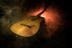 Abbildung der elektrischen Gitarre Akustikgitarre auf einem dunklen Hintergrund unter Lichtstrahl mit Rauche Gitarre mit Schnüren Lizenzfreie Stockfotos