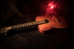 Abbildung der elektrischen Gitarre Akustikgitarre auf einem dunklen Hintergrund unter Lichtstrahl mit Rauche Gitarre mit Schnüren Stockfotos