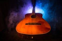 Abbildung der elektrischen Gitarre Akustikgitarre auf einem dunklen Hintergrund unter Lichtstrahl mit Rauche Gitarre mit Schnüren Lizenzfreies Stockbild
