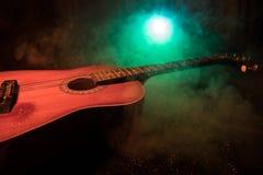 Abbildung der elektrischen Gitarre Akustikgitarre auf einem dunklen Hintergrund unter Lichtstrahl mit Rauche Gitarre mit Schnüren Lizenzfreie Stockbilder