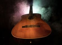 Abbildung der elektrischen Gitarre Akustikgitarre auf einem dunklen Hintergrund unter Lichtstrahl mit Rauche Gitarre mit Schnüren Lizenzfreies Stockfoto