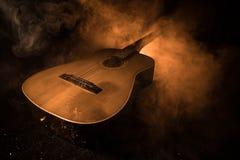 Abbildung der elektrischen Gitarre Akustikgitarre auf einem dunklen Hintergrund unter Lichtstrahl mit Rauche Gitarre mit Schnüren Stockbild