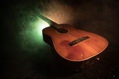 Abbildung der elektrischen Gitarre Akustikgitarre auf einem dunklen Hintergrund unter Lichtstrahl mit Rauche Gitarre mit Schnüren Stockbilder