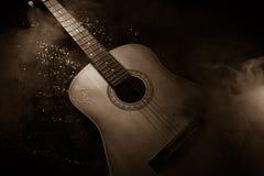 Abbildung der elektrischen Gitarre Akustikgitarre auf einem dunklen Hintergrund unter Lichtstrahl mit Rauche Gitarre mit Schnüren Stockfotografie