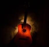 Abbildung der elektrischen Gitarre Akustikgitarre lokalisiert auf einem dunklen Hintergrund unter Lichtstrahl mit Rauche mit Kopi Stockfotos