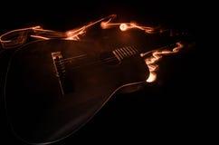 Abbildung der elektrischen Gitarre Akustikgitarre lokalisiert auf einem dunklen Hintergrund unter Lichtstrahl mit Rauche mit Kopi Stockbilder