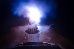 Abbildung der elektrischen Gitarre Akustikgitarre lokalisiert auf einem dunklen Hintergrund unter Lichtstrahl mit Rauche mit Kopi Lizenzfreies Stockfoto