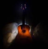 Abbildung der elektrischen Gitarre Akustikgitarre lokalisiert auf einem dunklen Hintergrund unter Lichtstrahl mit Rauche mit Kopi Stockbild