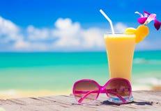 Abbildung der frischen Banane und des Ananassafts und der Sonnenbrille auf tropischem Strand Lizenzfreie Stockbilder