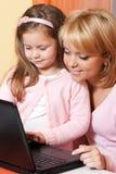 Abbildung der Mutter und des Kindes mit Laptop-Computer Lizenzfreies Stockfoto