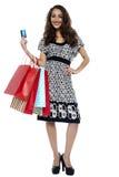 Abbildung der reizenden Frau mit Einkaufstaschen und -Kreditkarte Stockfoto