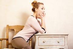 Abbildung der roten Lilie Mädchen, das am Retro- Schreibtisch sitzt Lizenzfreie Stockfotografie