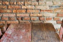 Abbildung der roten Lilie Wand des roten Backsteins mit hölzerner Tabelle Lizenzfreies Stockfoto