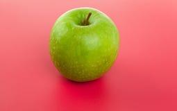 Abbildung des grünen Apfels auf Rot Lizenzfreies Stockbild