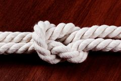 Abbildung Doppeltes acht weißes Seil auf dunkler Tabelle Stockfoto