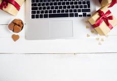 Abbildung kann als Hintergrund benutzt werden Computer, Geschenke und Plätzchen auf hölzerner Tabelle Stockfotos