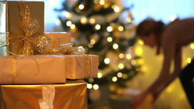 Abbildung kann als Hintergrund benutzt werden Junge Frau setzt die Geschenke unter den Weihnachtsbaum stock video footage