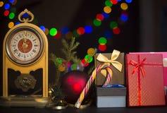 Abbildung kann als Hintergrund benutzt werden Weinleseuhr, Tannenbaumast, Geschenkboxen, Zuckerstange, roter Weihnachts-Ball auf  Stockbilder