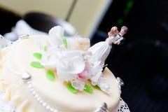 Abbildungen der Braut und des Bräutigams auf einem Hochzeitskuchen Lizenzfreies Stockfoto