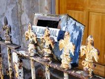 Abblätternde Farbe auf altem Metallpfosten-Zaun und Briefkasten Lizenzfreies Stockfoto