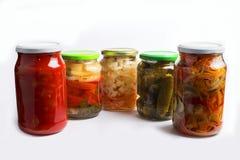 Abbondanza di bei barattoli di vetro con le insalate casalinghe di verdure isolate su fondo bianco Fotografia Stock Libera da Diritti