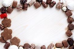 Abbondanza di cioccolato, di meringa e di biscotti di lavoro manuale su un fondo di legno leggero fotografia stock libera da diritti