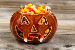 A abóbora fanged assustador encheu-se com o milho de doces na madeira rústica Imagem de Stock