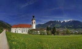 Abbotskloster i Fiecht, Tyrol, Österrike Sikt till abbotskloster och kyrkan med fjällängar i bakgrunden Royaltyfri Foto