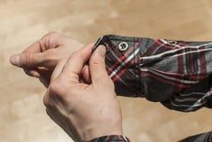 Abbottonare la manica del ` s della camicia Immagine Stock