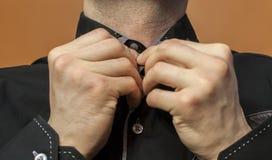 Abbottonare una camicia nera Fotografie Stock Libere da Diritti