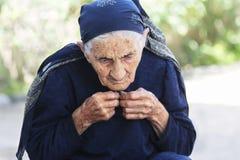 Abbottonarsi anziano della donna si veste in su Fotografie Stock