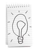 Abbozzo della lampadina sul taccuino a spirale Fotografie Stock Libere da Diritti