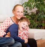 Abbracci di risata del nipote con la nonna Fotografie Stock