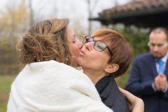 Abbracciando e baciando la sposa con lo sposo nel fondo Immagini Stock