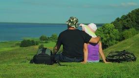 Abbracciando l'uomo e la donna stanno sedendo sull'orlo della montagna e dell'ammirare la vista del lago Fucilazione dalla parte  archivi video