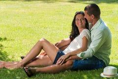 Abbracciando le coppie che si siedono nell'erba all'aperto Fotografie Stock Libere da Diritti
