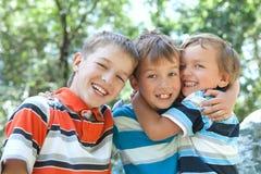 Abbracciare allegro dei tre fratelli Immagine Stock