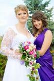 Abbracciare della damigella d'onore e della sposa Fotografia Stock