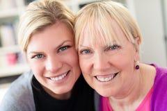 Abbracciare della figlia e della madre, esaminante macchina fotografica Immagine Stock