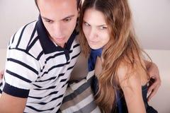 Abbracciare delle coppie, sedentesi sullo strato Fotografia Stock Libera da Diritti