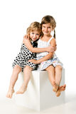 Abbracciare delle due ragazze isolato sopra priorità bassa bianca Fotografia Stock