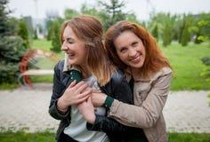 Abbracciare di risata di due donne Immagini Stock